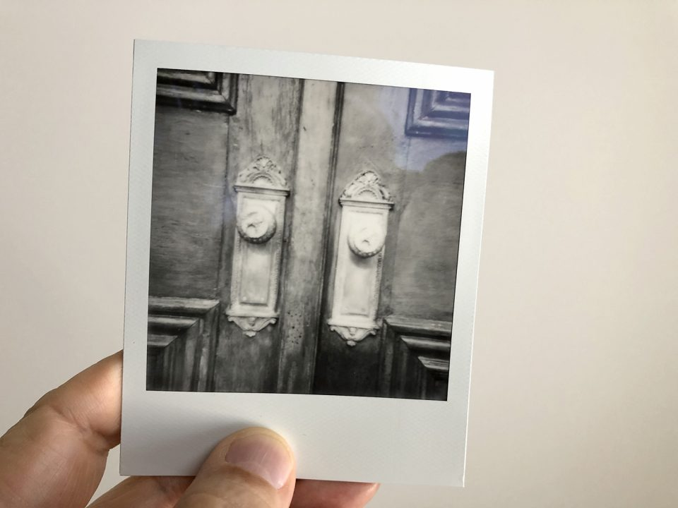 Black and white Polaroid photograph of decorative old door knobs, shot on SX-70 instant film. Photo by Keith Dotson.