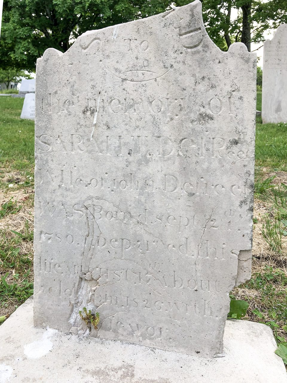 """Photograph of a broken headstone in the Riggs Crossroads Cemetery in Tennessee, that has been remounted in a cement base: """"Sacred to the memory of Sarah T. Defrees, Wife of John Defrees, was born'd Sept. 21th, 1780. Departed this life Aug. 17th about [time obscured] o'clock p.m. 1826 with a feavor"""""""