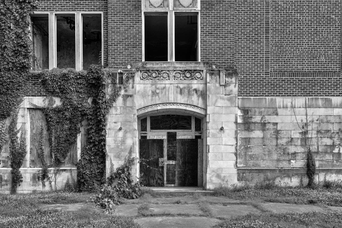 Doors to abandoned and boarded-up Clarksdale High School in Clarksdale, Mississippi. Black and white photograph by Keith Dotson.