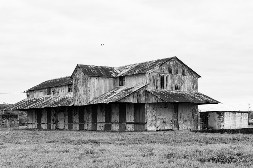 Mississippi Delta cotton gin with airplane flying past. Black and white photograph by Keith Dotson. Buy a fine art print here.