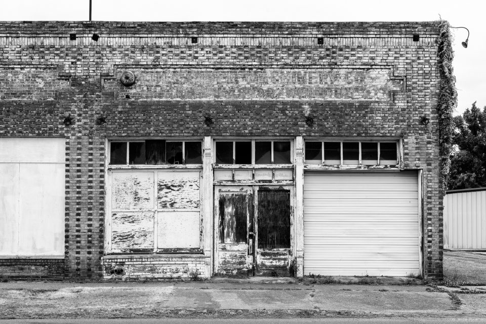 Black and white photograph of the front of the abandoned Cullander Machinery building found in Belzoni, Missisippi