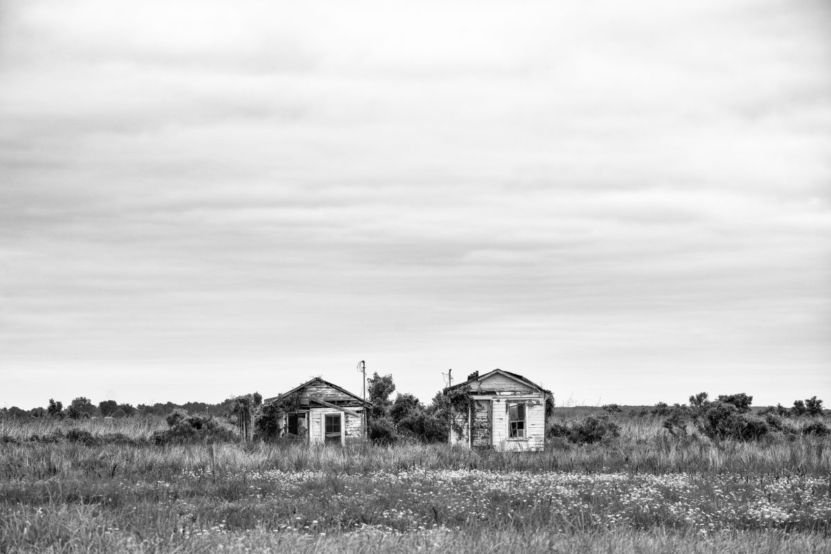 Abandoned shotgun shacks located on the highway between Clarksdale and Belzoni, Mississippi. Black and white photograph by Keith Dotson. Buy a fine art print.