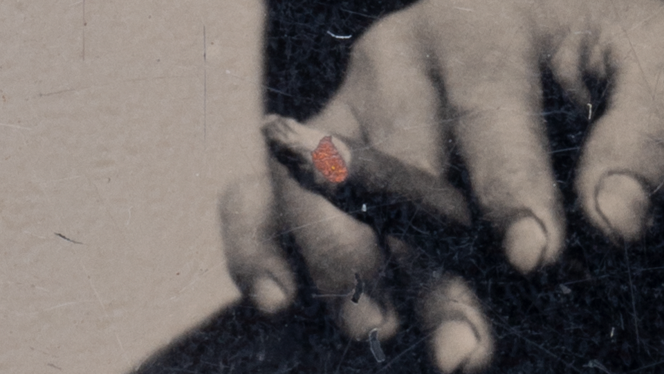 This close-up look at the subject's hand shows the dirt around his fingernails -- a working man -- and the fleck of rust that looks like retouched fire on his cigar.