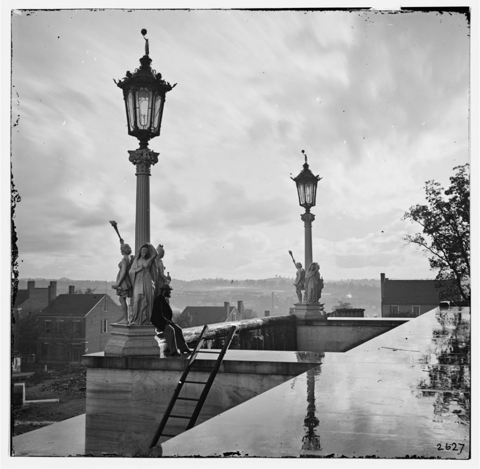 """The Lady of the Falls seen in 1865 in her previous life as the statue """"Night,"""" (part of Morning, Noon, and Night) around lampposts on the grounds of the Tennessee State Capitol in Nashville. """"Nashville, Tennessee. View from Capitol."""" Photograph by George N. Barnard. Library of Congress."""