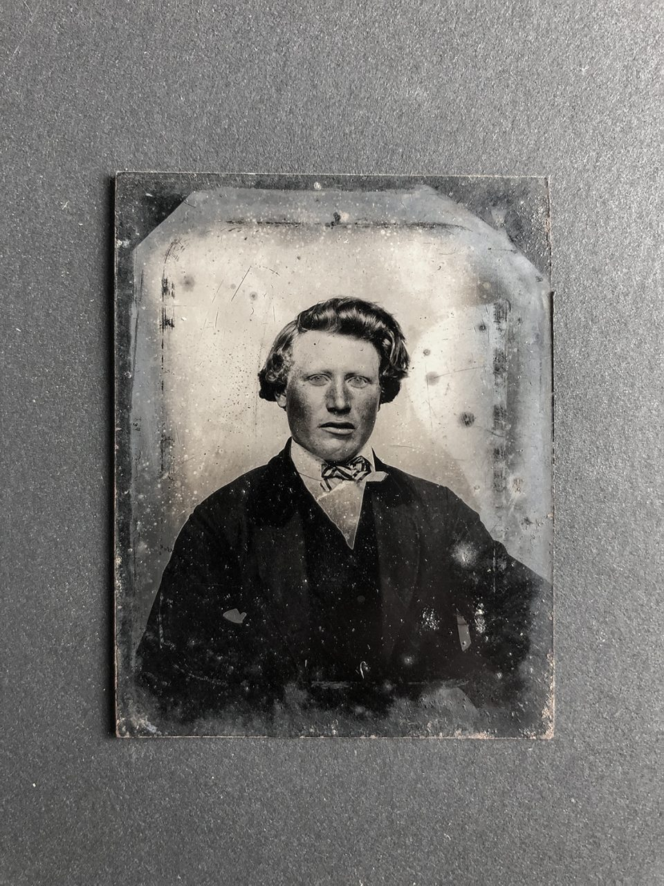Tintype portrait of a young man, probably circa late 1850s or early 1860s (based on his hairstyle and clothing). The print displays signs of corrosion. Keep in mind that tintypes were unique originals, meaning there was no negative. This is the only version of this photograph in existence.