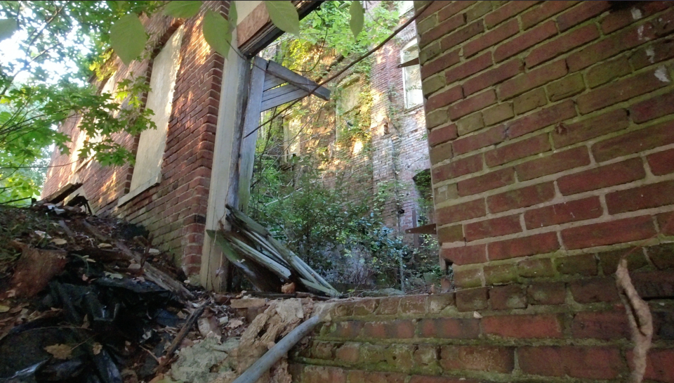 Peeking into the window of the abandoned old mill, you can see the sunrise glowing warm on the distant wall.